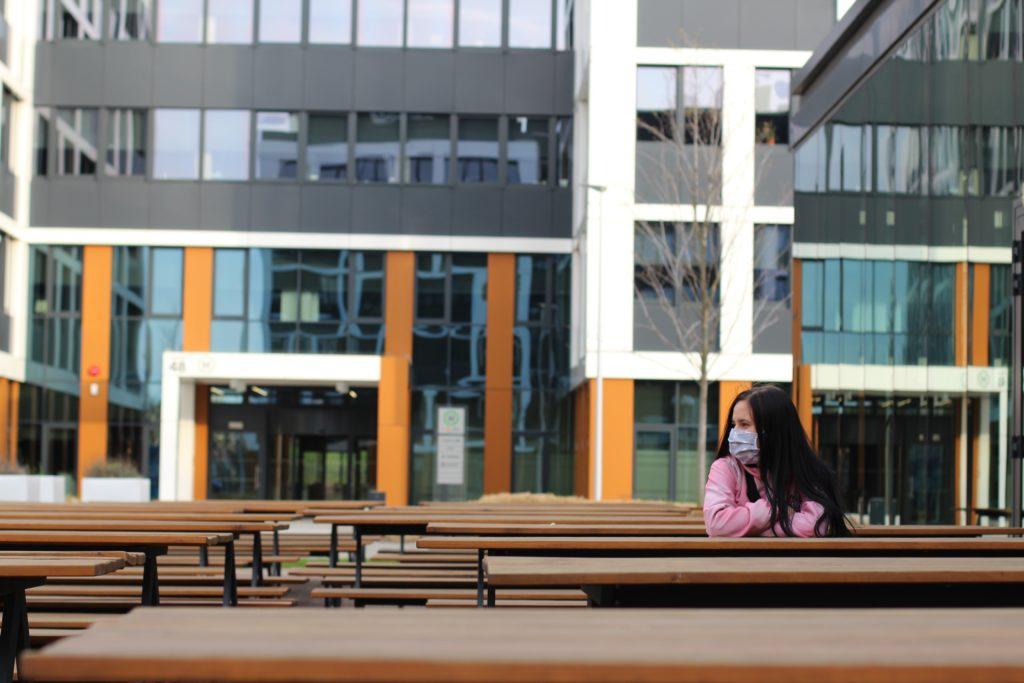 Frau mit Masje sitzt alleine im Freien in einer Tischgruppe